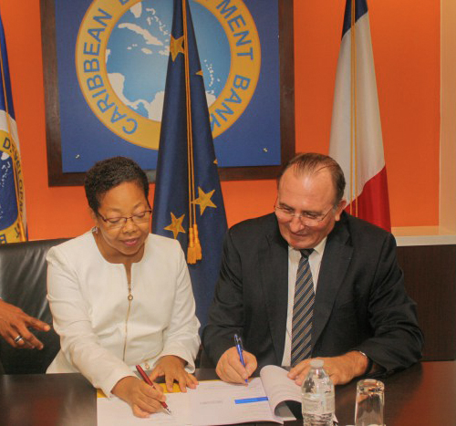 Patricia McKenzie, CDB Vice-President, Operations and Eric de la Moussaye, French Ambassador to the Organisation of Eastern Caribbean States and Barbados, sign the Credit Facility Agreement.