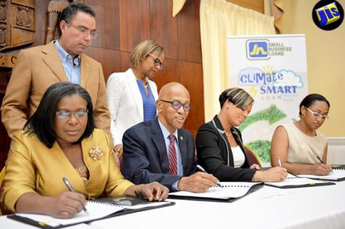 Minister without Portfolio in the Ministry of Economic Growth and Job Creation, Hon. Daryl Vaz (standing, left) and General Manager, Country Department, Caribbean Group, Inter-American Development Bank, Therese Turner Jones