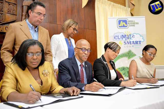 Minister without Portfolio in the Ministry of Economic Growth and Job Creation, Hon. Daryl Vaz (standing, left) and General Manager, Country Department, Caribbean Group, Inter-American Development Bank, Therese Turner Jones (standing, right), observe as (from left) Permanent Secretary in the Ministry of Economic Growth and Job Creation, Audrey Sewell; Managing Director, Development Bank of Jamaica, Milverton Reynolds; General Manager, JN Small Business Loans, Gillian Hyde; and Programme Manager, Environmental Foundation of Jamaica (EFJ), Allison Rangolan McFarlane sign the Memorandum of Understanding (MOU) for the Adaptation Programme and Financing Mechanism Project at Jamaica House, in St. Andrew, on July 28. Under the initiative, US$7.2 million will be made available to micro, small and medium-size enterprises (MSMEs) in the tourism and agricultural sectors to finance climate-change adaptation initiatives islandwide.