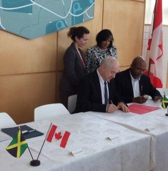 Dr. Kim Dotto, British Columbia Institute of Technology (seated – first left) signs MOU with Dr. Gary Jackson, emPOWERed Caribbean Communities. The signing was witnessed by Mrs. Julie Forrest, Senior Trade Commissioner at the High Commission of Canada in Jamaica and Mrs. Hillary Alexander, Permanent Secretary, Ministry of Energy, Science and Technology, Jamaica. (Photo: Canadian High Commission/Jamaica)